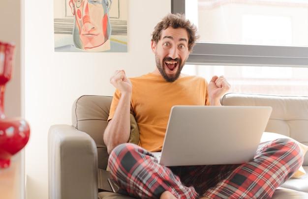 Jovem barbudo se sentindo chocado, animado e feliz, rindo e comemorando o sucesso, dizendo uau e sentado com um laptop