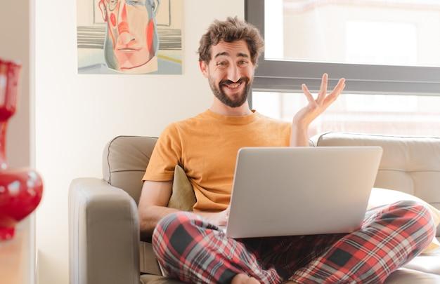 Jovem barbudo se sentindo feliz surpreso e alegre, sorrindo com atitude positiva, percebendo uma solução ou ideia e sentado com um laptop