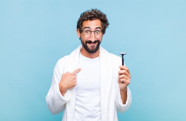 Jovem barbudo se sentindo feliz, surpreso e orgulhoso, apontando para si mesmo com um olhar animado e surpreso
