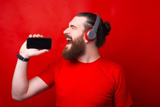 Jovem barbudo segurando um smartphone, assinando e ouvindo música em fones de ouvido na parede vermelha