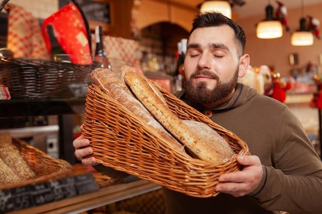 Jovem barbudo segurando uma cesta cheia de deliciosos pães recém-assados, fazendo compras na padaria