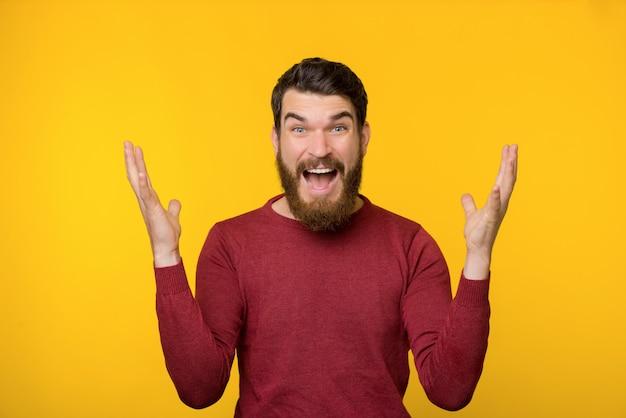 Jovem barbudo sendo surpreendido perto da parede amarela.