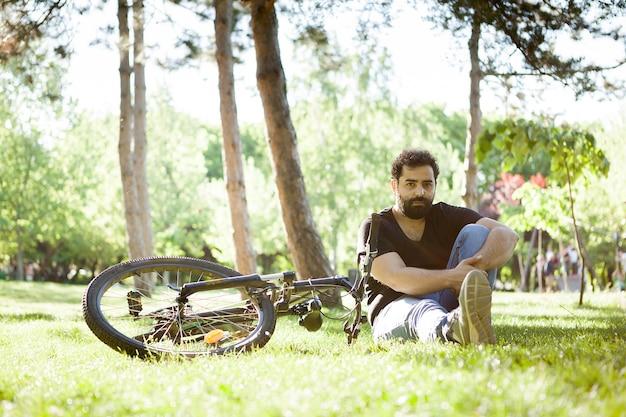 Jovem barbudo sentado na grama do parque ao lado de sua bicicleta