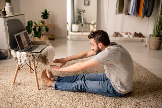 Jovem barbudo sentado no chão da sala de estar curvando-se enquanto ouve o professor de ioga online