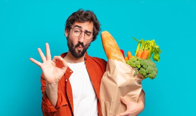Jovem barbudo sentindo-se feliz, relaxado e satisfeito, mostrando aprovação com um gesto de ok, sorrindo e segurando uma sacola de legumes