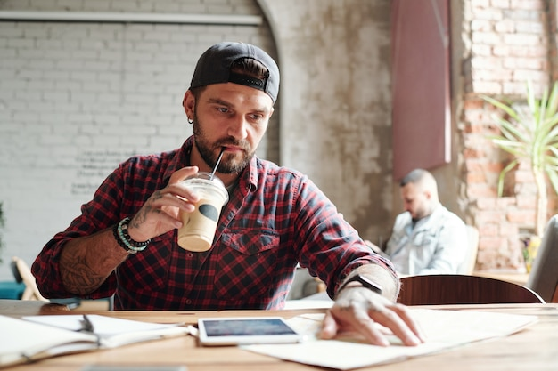 Jovem barbudo sério com boné bebendo café frio e verificando lugares no mapa de papel em um café