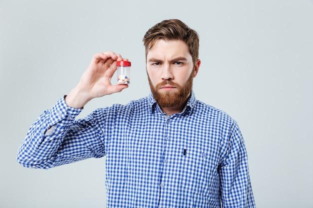 Jovem barbudo sério segurando comprimidos em uma garrafa sobre a parede branca