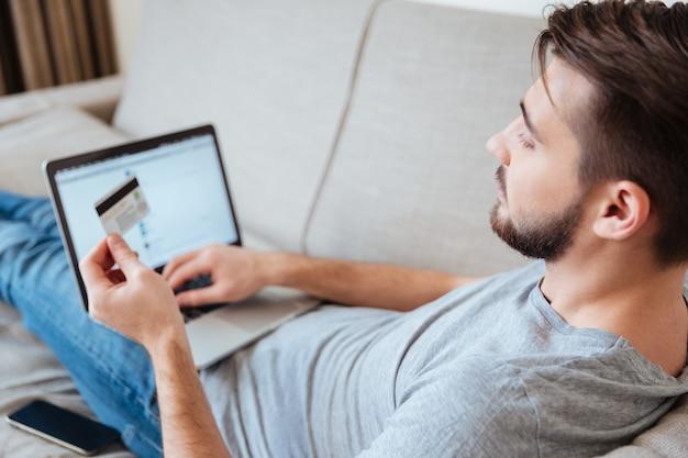 Jovem barbudo sério usando cartão de crédito e laptop para fazer compras online, deitado no sofá em casa