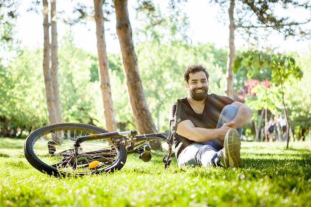 Jovem barbudo sorri para a câmera sentada no chão na grama do parque. sua bicicleta está ao lado dele no chão