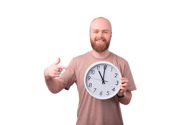 Jovem barbudo sorridente e alegre apontando para o relógio de parede branco