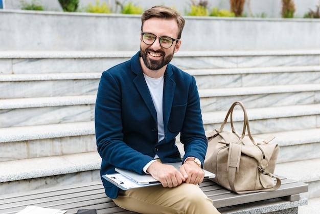 Jovem barbudo sorridente e bonito vestindo uma jaqueta segurando um laptop enquanto está sentado ao ar livre no banco da cidade