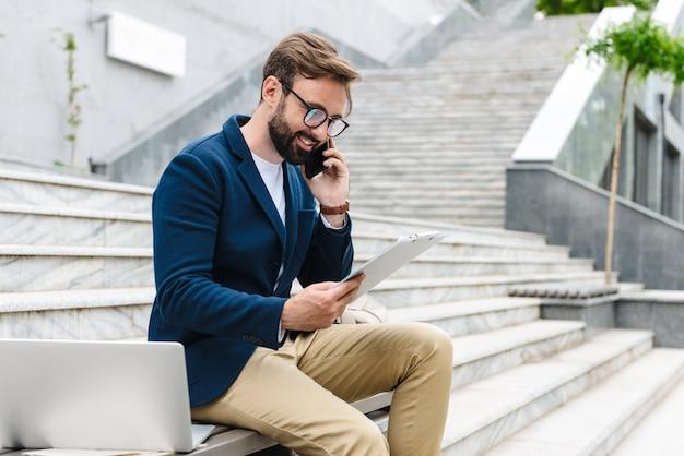 Jovem barbudo sorridente e bonito vestindo uma jaqueta, sentado em um banco e falando no celular enquanto olha documentos