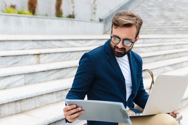 Jovem barbudo sorridente e bonito vestindo uma jaqueta, trabalhando em um laptop, enquanto está sentado ao ar livre no banco da cidade, analisando documentos