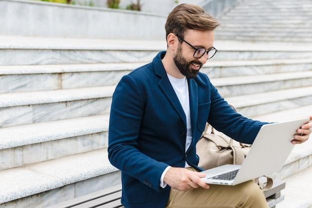 Jovem barbudo sorridente e bonito vestindo uma jaqueta, trabalhando em um laptop, enquanto está sentado ao ar livre no banco da cidade