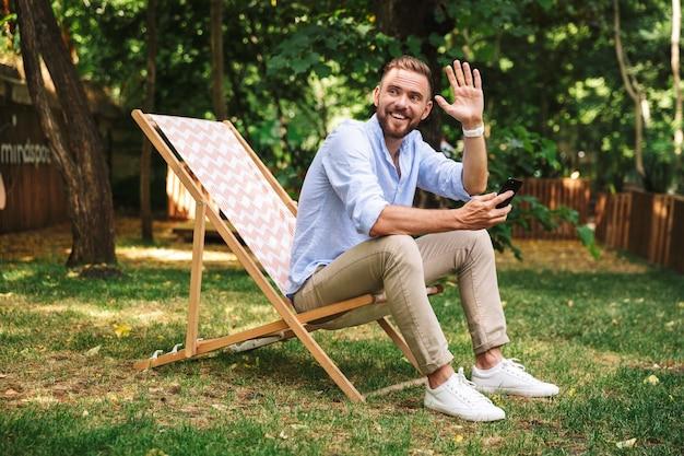 Jovem barbudo sorridente e emocional usando telefone celular