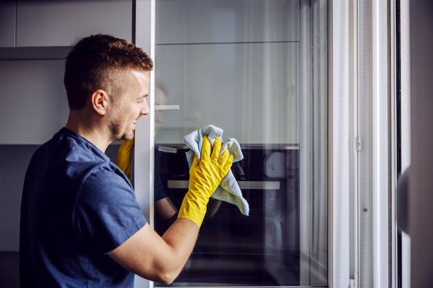 Jovem barbudo sorridente homem positivo com luvas de borracha, limpando a janela com um pano. depois da chuva, sempre há manchas no vidro.