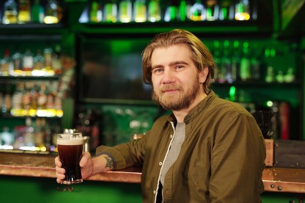 Jovem barbudo sorridente, vestindo roupas casuais, olhando para você em pé na frente da câmera contra o bar com bebidas alcoólicas e tomando um copo de cerveja