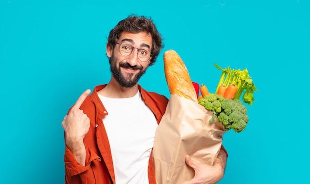 Jovem barbudo sorrindo com confiança apontando para o próprio sorriso largo, atitude positiva, relaxada, satisfeita e segurando uma sacola de legumes