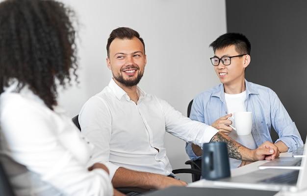 Jovem barbudo sorrindo e falando com colegas multirraciais enquanto está sentado na mesa durante o intervalo no escritório