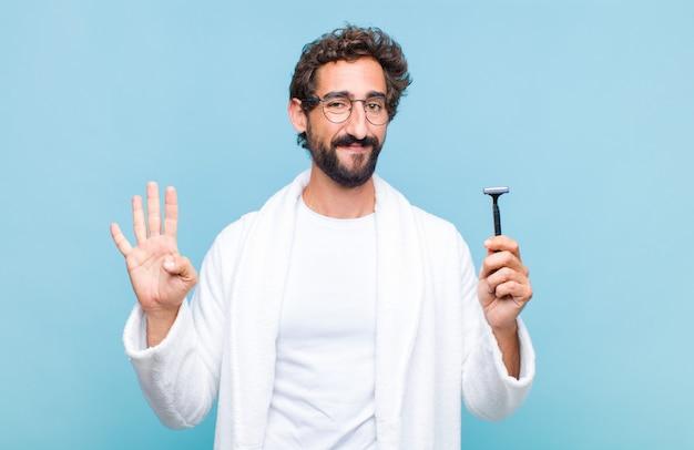 Jovem barbudo sorrindo e parecendo amigável, mostrando o número quatro ou o quarto com a mão para a frente, em contagem regressiva
