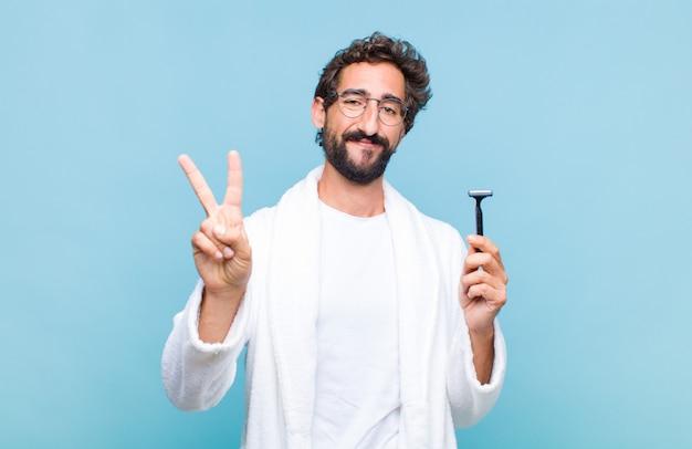 Jovem barbudo sorrindo e parecendo feliz, despreocupado e positivo, gesticulando vitória ou paz com uma mão