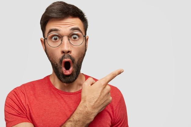 Jovem barbudo surpreso com os olhos saltados, expressão de espanto, aponta para o lado no espaço da cópia em branco