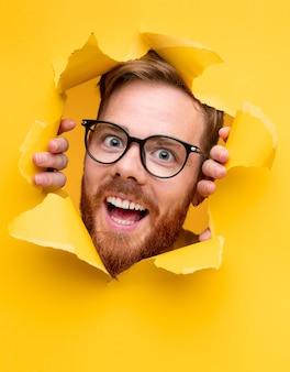 Jovem barbudo surpreso e positivo com óculos espiando de um papel amarelo rasgado