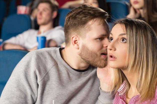 Jovem barbudo sussurrando para sua mulher chocada no cinema no cinema local