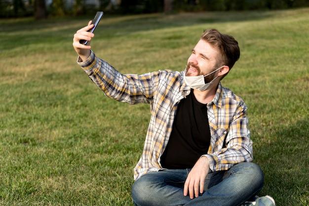 Jovem barbudo tirando uma selfie