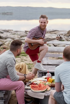 Jovem barbudo tocando violão e sorrindo feliz enquanto passa a noite de verão com amigos ao ar livre à beira do lago
