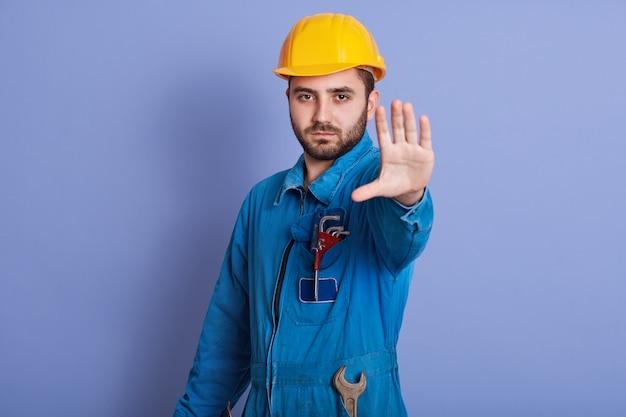 Jovem barbudo trabalhador bonito com capacete amarelo e uniforme fazendo o gesto de parada com a mão, negando a situação