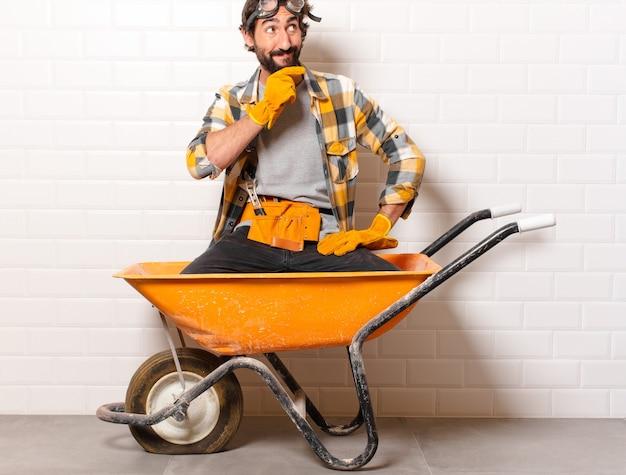 Jovem barbudo trabalhador da construção civil em um carrinho de mão