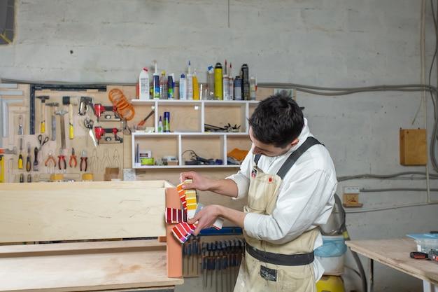 Jovem barbudo trabalhando na fábrica de móveis, combinação de cores para móveis