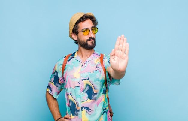 Jovem barbudo turista homem olhando sério, severo, descontente e irritado, mostrando a palma da mão aberta fazendo gesto de pare