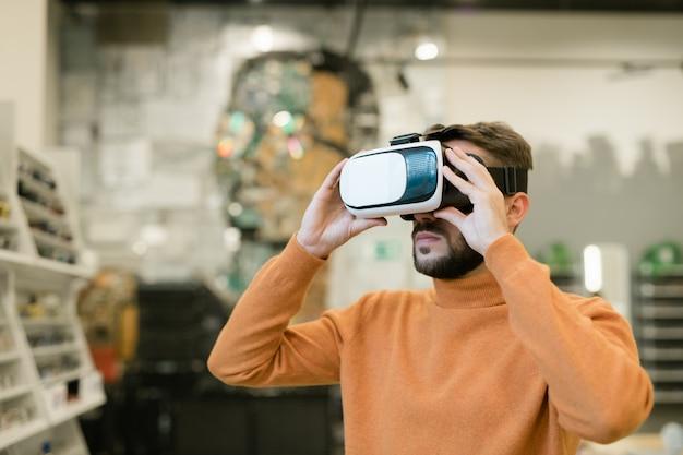 Jovem barbudo usando fone de ouvido vr dentro da loja de ótica contemporânea e escolhendo novos óculos no uso do visor virtual