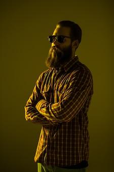 Jovem barbudo usar óculos escuros com as mãos cruzadas