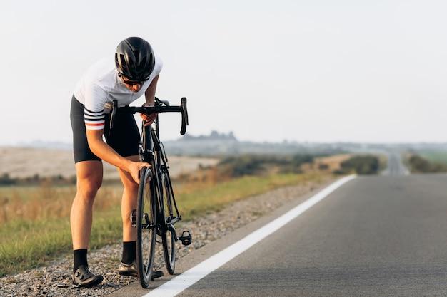Jovem barbudo vestido com roupas esportivas, verificando as condições da roda da bicicleta antes de andar em uma estrada asfaltada
