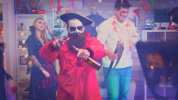 Jovem barbudo vestido de pirata se divertindo na festa de halloween.