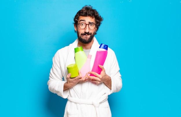Jovem barbudo vestindo roupão de banho com shampoo e produtos de beleza