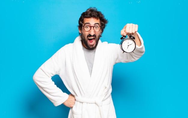 Jovem barbudo vestindo roupão de banho e despertador