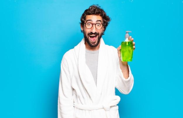 Jovem barbudo vestindo roupão de banho e shampoo