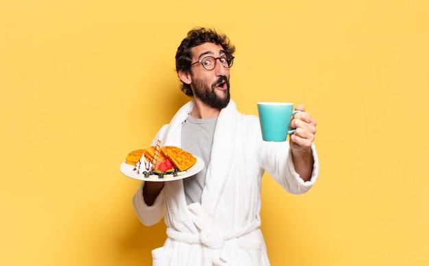 Jovem barbudo vestindo roupão de banho e tomando café da manhã