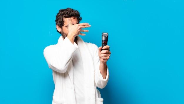 Jovem barbudo vestindo roupão de banho fazendo a barba.
