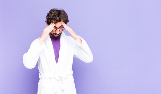 Jovem barbudo vestindo roupão de banho, parecendo estressado e frustrado, trabalhando sob pressão, com dor de cabeça e preocupado com problemas