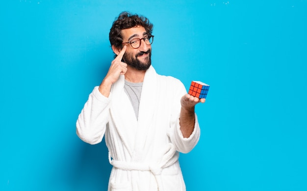 Jovem barbudo vestindo roupão de banho, resolvendo um problema de inteligência