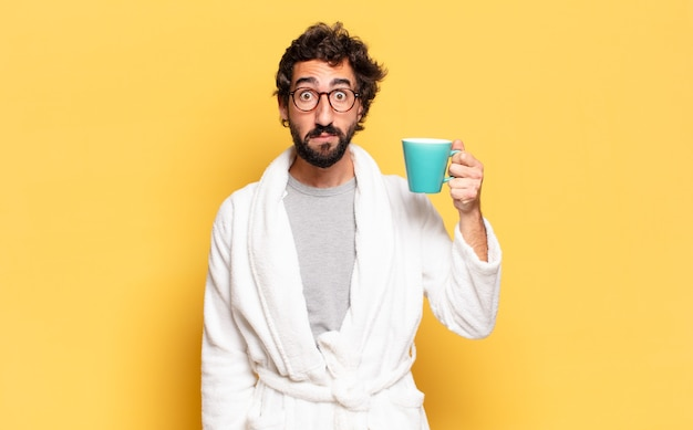 Jovem barbudo vestindo roupão de banho segurando uma xícara de café