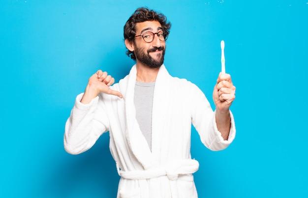 Jovem barbudo vestindo roupão e escova de cabelo