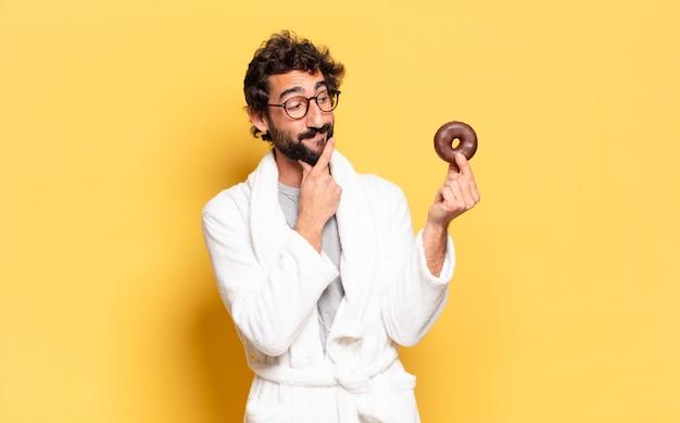 Jovem barbudo vestindo roupão e um donut de chocolate