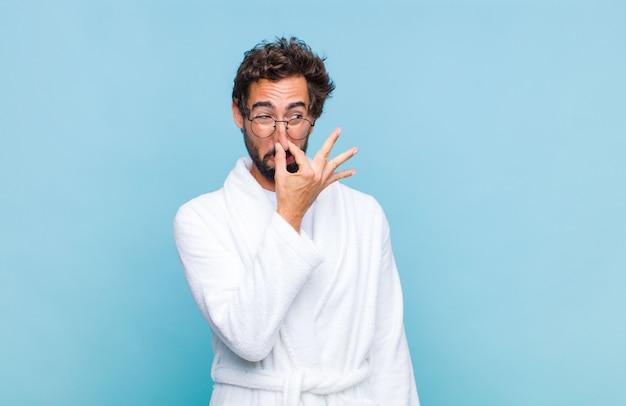 Jovem barbudo vestindo um roupão de banho e sentindo nojo
