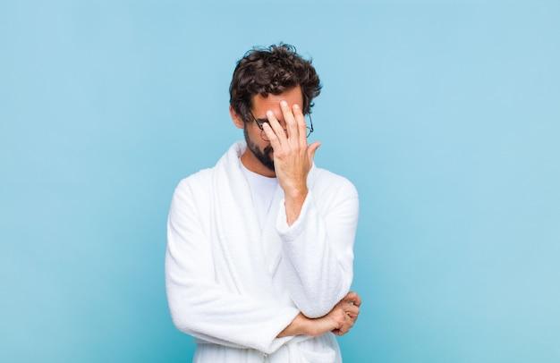 Jovem barbudo vestindo um roupão de banho, parecendo estressado, envergonhado ou chateado, com dor de cabeça, cobrindo o rosto com a mão